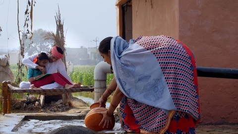 A village lady fills water for daily work while her husband helps daughter in studies