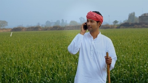 A confident modern farmer making a call while standing in his agricultural field