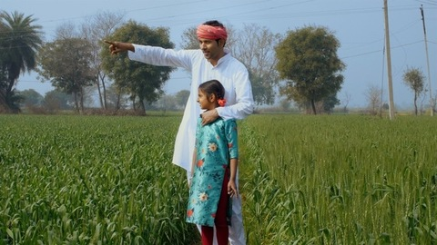 An Indian farmer is happy to show the agricultural land to his young daughter