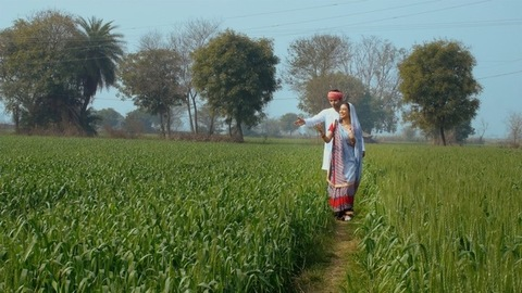 An Indian farmer is happy to show the agricultural land to his young housewife