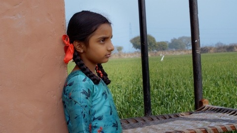 An upset small village girl stares out towards a field - the loneliness of a child concept