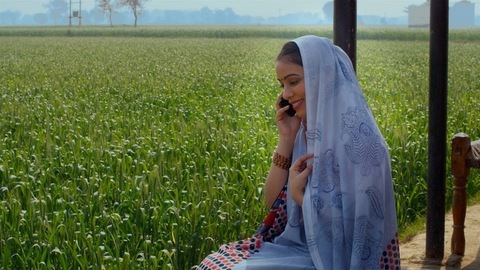 An Indian laborer talking to her husband on a smartphone while sitting in the fields