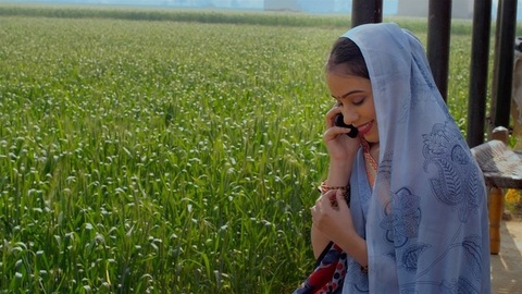 A shy woman in a traditional saree talking to her relatives using a mobile sitting in a field