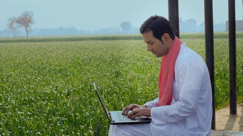 Educated Indian farmer learning new things on a laptop - technology concept