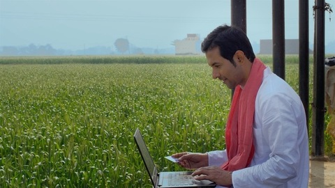 Handsome Indian villager doing card payment via laptop - online shopping concept
