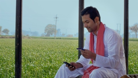 A young Indian farmer using a credit card to make an online payment through a smartphone