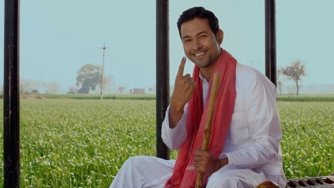 A happy farmer showing his ink-marked finger and his belief in the right to vote