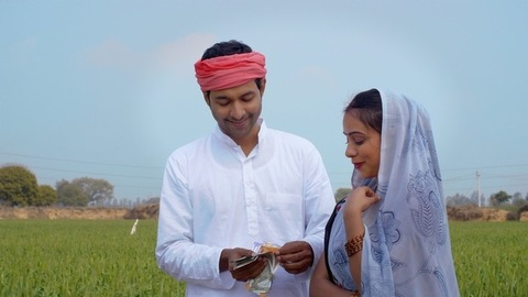 North Indian farmer and his wife counting their last month's hard-earned money