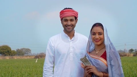 Middle-aged Indian farmer giving his hard-earned income to his beautiful wife