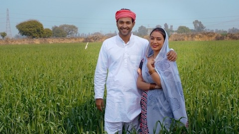 Village Scene - Indian village couple smiling while standing in their green fields