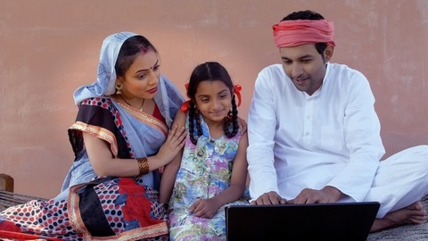 Educated Indian farmer teaching the usage of a laptop to his wife and daughter