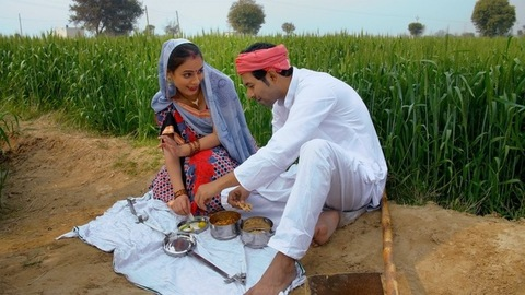 Happy village couple having food together during a break from agricultural work