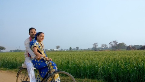 Indian village happy couple enjoying a bicycle ride near the agricultural fields
