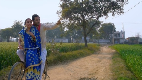 Married village couple enjoying a bicycle ride together in their agricultural land