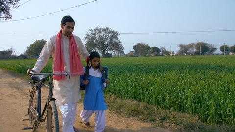 A young village farmer taking his girl child to school. Beti bachao beti padhao