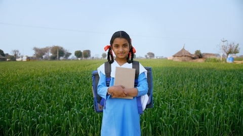 Well-dressed village school girl smiling while standing in her agricultural field