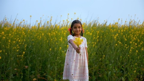 Portrait of a little village girl happily showing a bunch of beautiful yellow flowers