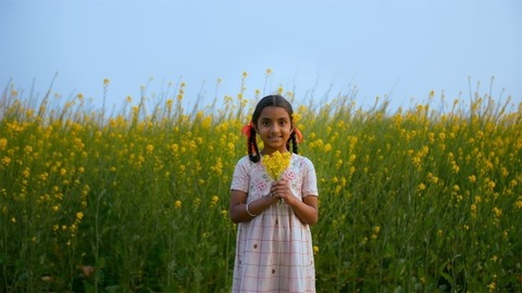 Farmer's young daughter standing in mustard or Sarso field smelling the fresh air