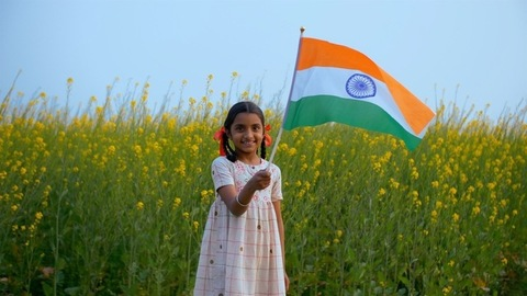 Young village girl proudly swinging the Indian flag while standing in a mustard farm
