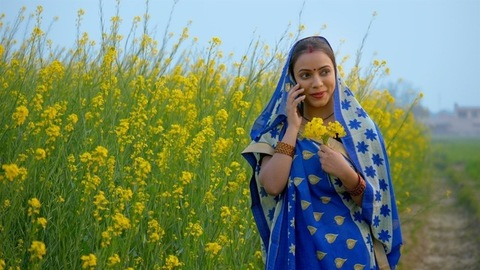 Married Indian woman talking on mobile while holding a bunch of mustard flowers