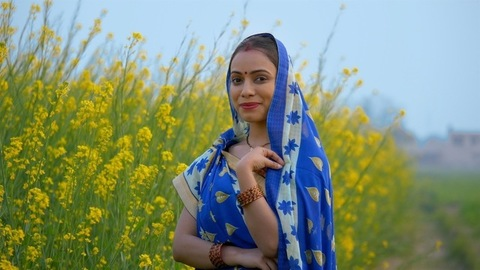 Beautiful village woman smiling and posing in front of a mustard/Sarso field