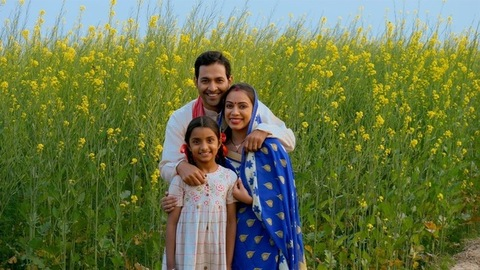 Cheerful Indian village family standing in front of their mustard (Sarso) field