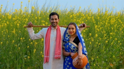 Handsome farmer and his wife in traditional dresses standing in their mustard  or sarso field