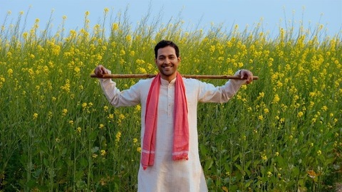 Portrait of a confident smiling farmer standing with a stick in his mustard field