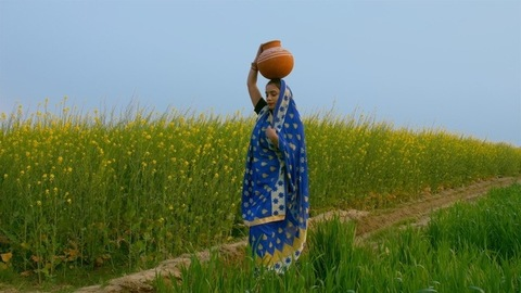 An Indian village woman carrying a pitcher (Ghara) full of water on her head