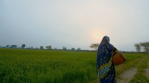 Village scene - Beautiful married woman walking through a field with a clay pot