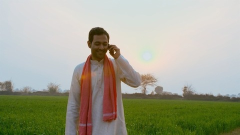 A smiling Indian farmer talking on mobile while standing near a green farmland