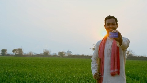 Pan shot of a confident Indian farmer happily showing his new debit or credit card