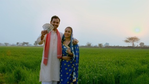 Village scene - Indian married couple happily showing their hard-earned money