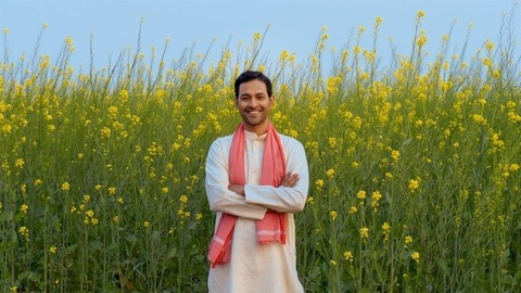 Portrait of a happy Indian farmer standing in his agricultural field (mustard farm)
