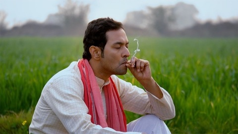 Young North Indian farmer smoking Bidi or Beedi in his green agricultural farm