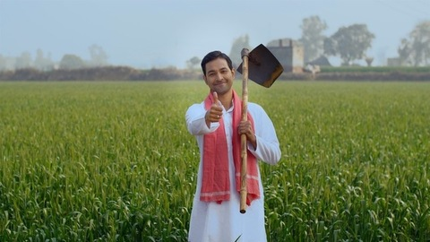 A young happy farmer with a shovel (phawra) in his village farm