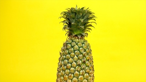 Fresh nutritional pineapple rotating / spinning against a colorful background