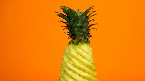 A peeled pineapple with its green stalk on top against a colorful background