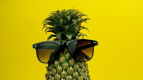 Fresh and plump pineapple wearing black sunglasses - summer vacation concept