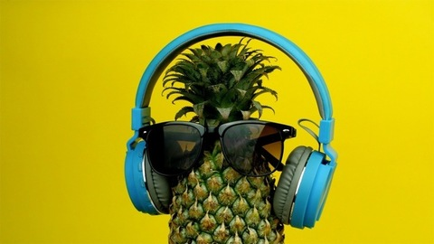 Whole unpeeled pineapple with sunglasses and headphone listening to music