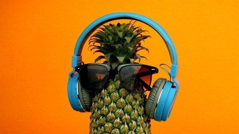 Pineapple with eyewear and headphone rotating slowly against an orange background