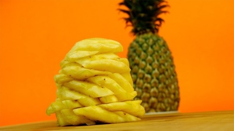 Pan shot of peeled and cut ripe yellow pineapple against a colorful background