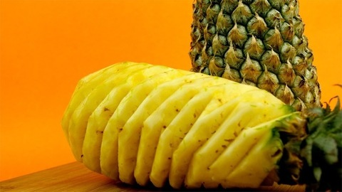 One peeled and one uncut ripe pineapple rotating against an orange background