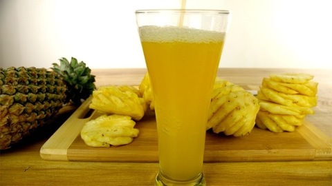 A big glass filling up with refreshing juice with chunks of pineapple placed behind - Pineapple juice