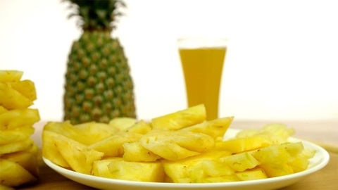 A plate with juicy yellow pineapple pieces rotating on a table - antioxidant fruit
