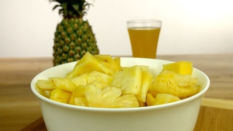 Zoom in shot of a bowl full of fresh and juicy pineapple slices - healthy fruit