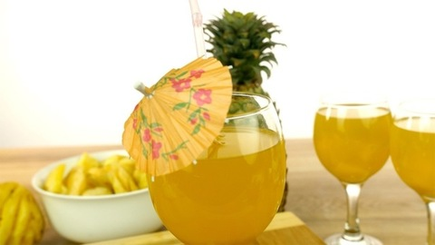 Tilt view of healthy cool summer drink with a whole pineapple and its slices