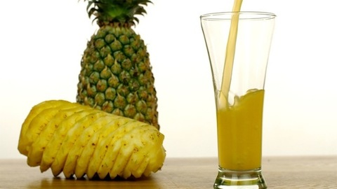 Freshly prepared juice with peeled and unpeeled pineapples placed nearby