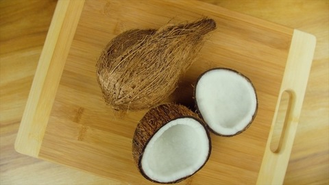 A brown hairy coconut and two halves of a coconut rotating on a wooden platform