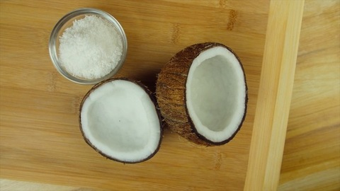 Two halves of a coconut and a coconut flakes bowl rotating on a wooden platform